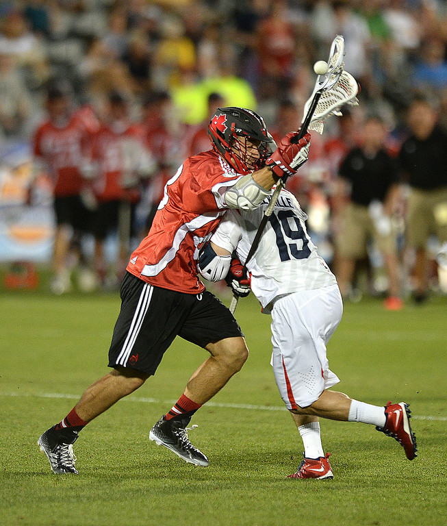 . United States attack Kevin Leveille (19) put a hit on Canada defenseman Matt Vinc (48) to cause a turnover in the second half. The United States defeated Canada 10-7 in the opening game of the FIL World Lacrosse Championships Thursday night, July 10, 2014.   Photo by Karl Gehring/The Denver Post