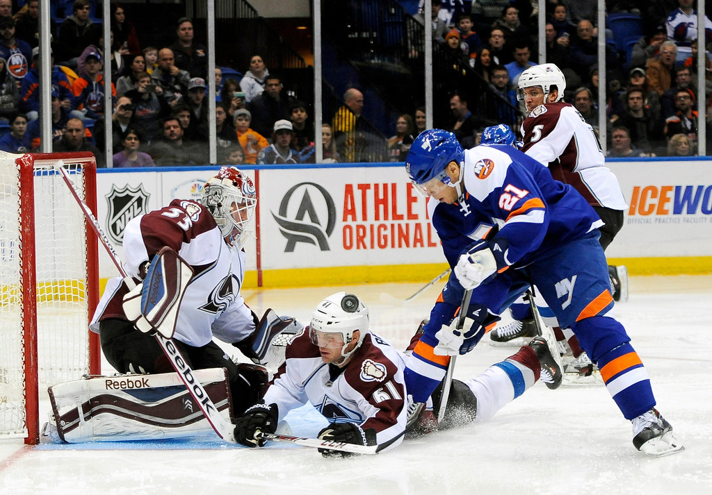 . Colorado Avalanche goalie Jean-Sebastien Giguere (35) defends as Andre Benoit (61) falls to the ice against New York Islanders\' Kyle Okposo (21) in the second period of an NHL hockey game on Saturday, Feb. 8, 2014, in Uniondale, N.Y. (AP Photo/Kathy Kmonicek)