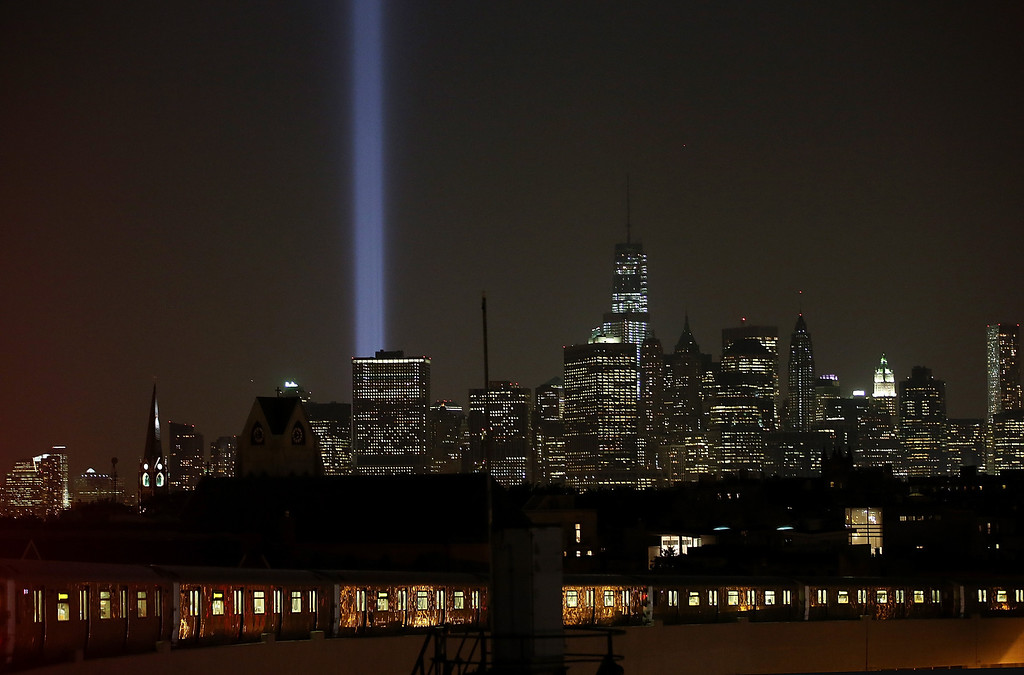 . NEW YORK, NY - SEPTEMBER 10:  New York City\'s Tribute In Light shines near One World Trade Center (Top, R) in Manhattan on the eve of the twelfth anniversary of the terrorist attacks at the World Trade Center on September 10, 2013 in New York City. New York City and the nation will commemorate the eleventh anniversary of the September 11, 2001 attacks, which resulted in the deaths of nearly 3,000 people after two hijacked planes crashed into the World Trade Center towers, one into the Pentagon in Arlington, Virginia and one into a field outside OF Shanksville, Pennsylvania.  (Photo by Mario Tama/Getty Images)