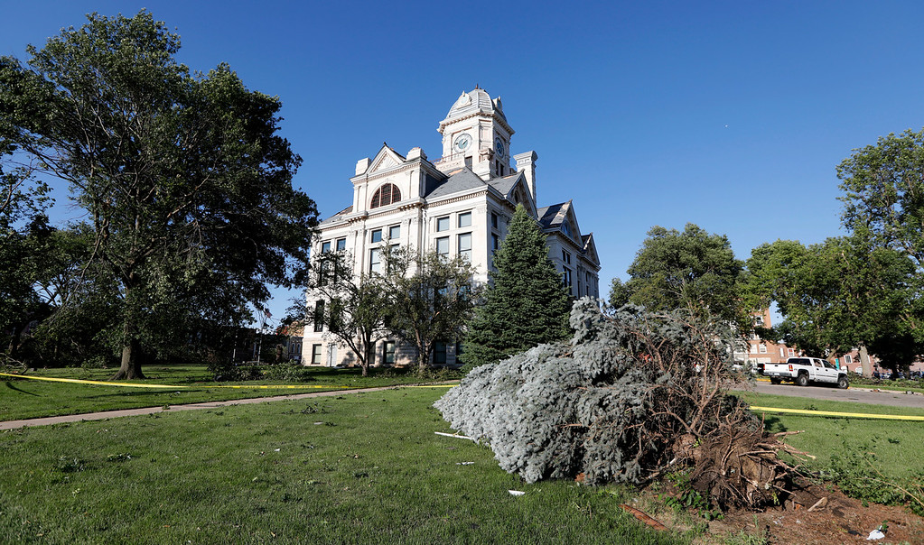 . An uprooted tree lies in front of the tornado damaged Marshall County Courthouse, Thursday, July 19, 2018, in Marshalltown, Iowa. Several buildings were damaged by a tornado in the main business district in town including the historic courthouse. (AP Photo/Charlie Neibergall)