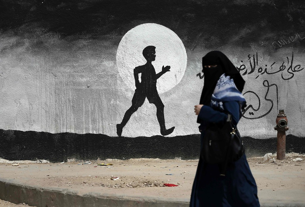 . A Palestinian woman walks past a graffiti painted on a wall of the United Nations school of Beit Hanun, in the northern Gaza Strip, on May 9, 2016. THOMAS COEX/AFP/Getty Images