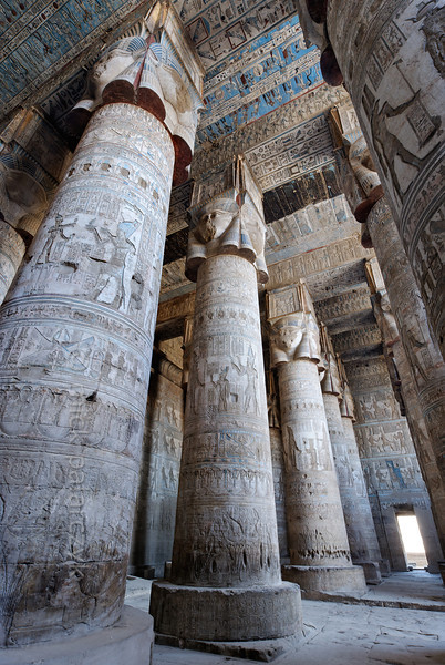 """[EGYPT 29515] 'Outer hypostyle hall of Hathor Temple at Dendera.'  The columns in the outer hypostyle hall (or pronaos) of the Hathor Temple at Dendera are crowned by four-sided capitals carved with the face of the cow-eared goddess. The faces symbolize the four cardinal points of the universe and stress the universal character of the sky goddess Hathor, who was also called """"Lady with the four Faces"""". The square structure that is placed on top of the actual face is a sistrum, a ritual musical instrument that produced a rustling sound that was thought to please Hathor. The ceiling of the hall has recently been cleaned of soot and dust and is decorated with a complex set of astronomical figures, constellations, planets and a zodiac. The shafts of the columns bear the image of a pharaoh (recognizable by his blue crown) who can be identified by his cartouches as the Roman emperor Claudius. This part of the Dendera Temple was built during the Roman period (first century AD). Photo Mick Palarczyk."""