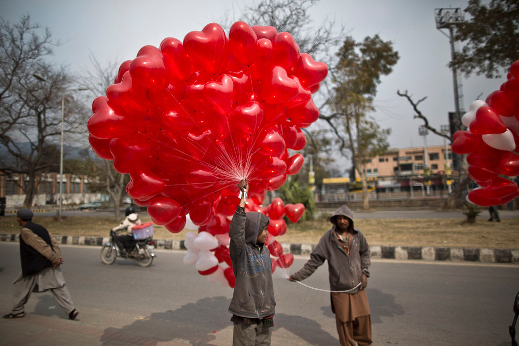 . A Pakistani boy stands on a roadside along with other vendors, holding red heart-shaped balloons hoping to sell them on Valentine\'s Day in Islamabad, Pakistan, Friday, Feb. 14, 2014. (AP Photo/Muhammed Muheisen)
