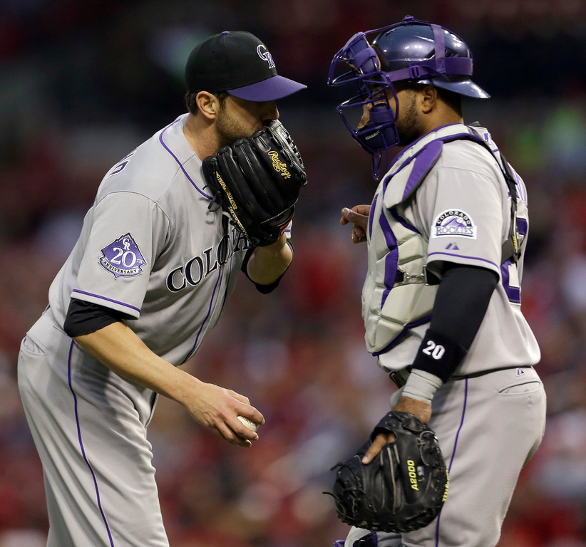 . Colorado Rockies starting pitcher Jon Garland, left, talks with catcher Wilin Rosario during the second inning of a baseball game against the St. Louis Cardinals, Friday, May 10, 2013, in St. Louis. (AP Photo/Jeff Roberson)
