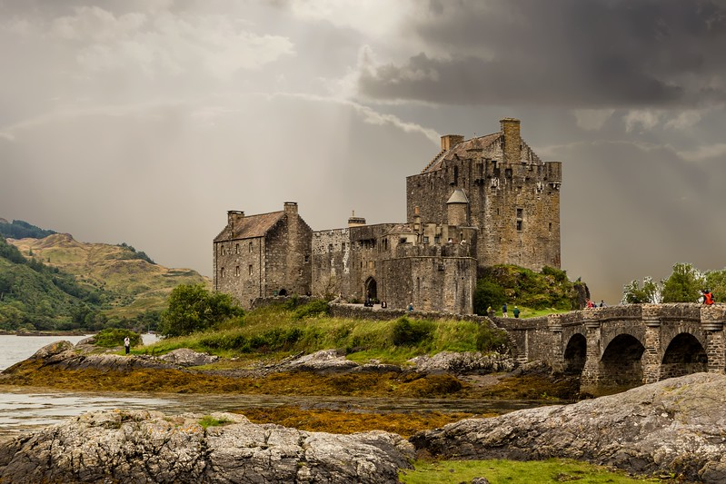 A castle is surrounded by moody skies and a green landscape on a road trip in Scotland.