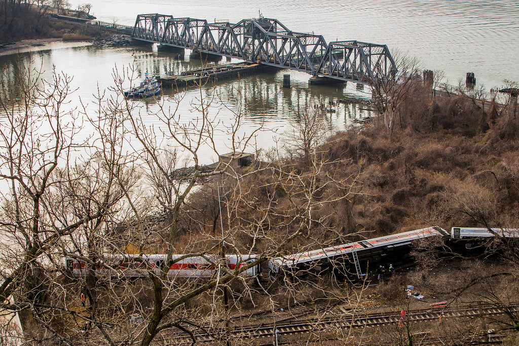 . A Metro-North commuter train lies in the brush after it derailed just north of the Spuyten Duyvil station December 1, 2013 in the Bronx borough of New York City. Multiple injuries and at least 4 deaths were reported after the seven car train left the tracks as it was heading to Grand Central Terminal along the Hudson River line.  (Photo by Christopher Gregory/Getty Images)