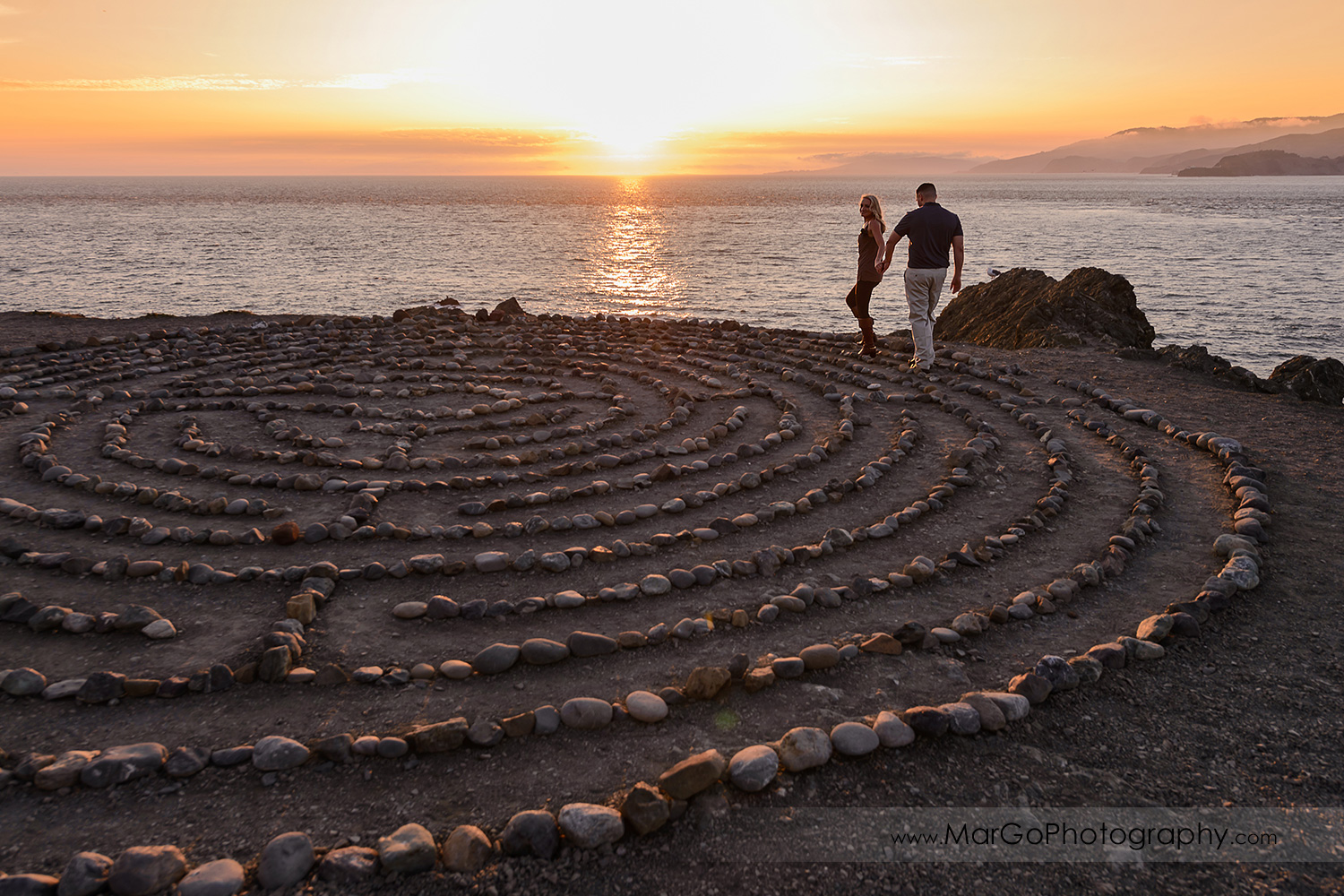 man in navy blue shirt and woman in brown tunic walking in the stone labyrinth during sunset engagement session at San Francisco Lands End
