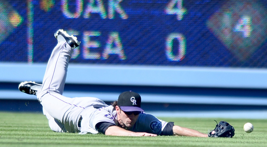 . Rockies\' Charlie Culberson #23 dives for a Juan Uribe single hit in the fifth as the Rockies defeat the Dodgers 2-1 at Dodger Stadium during their final game of the regular season Sunday, September 29, 2013. (Photo by Sarah Reingewirtz/Pasadena Star-News)
