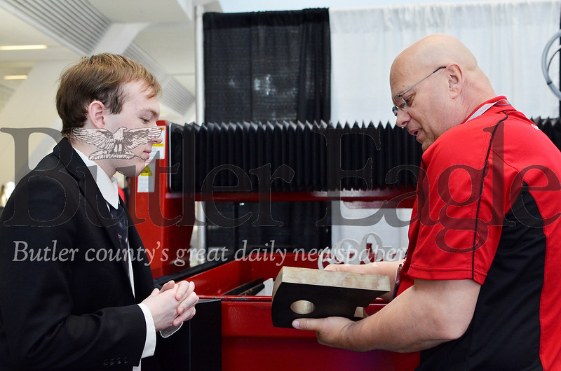 Sean Wallace, 18, a senior at Moniteau High School talks to Jeff Gates of Koike Aronson Inc. about waterjet cutting machines at the 2019 Association for Iron and Steel Technology Conference in Pittsburgh. Tanner Cole/Butler Eagle
