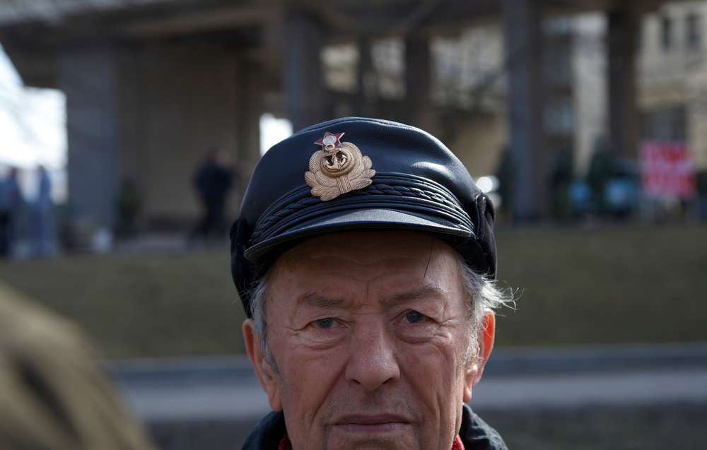 . A man wears a hat with Soviet Navy emblem and the red star on it as he and others gather outside the Parliament building in Simferopol, Ukraine, Saturday, March 1, 2014. The discord between Russia and Ukraine sharpened Saturday when the pro-Russian leader of Ukraine\'s Crimea region claimed control of the military and police and appealed to Russia\'s president for help in keeping peace there. (AP Photo/Ivan Sekretarev)