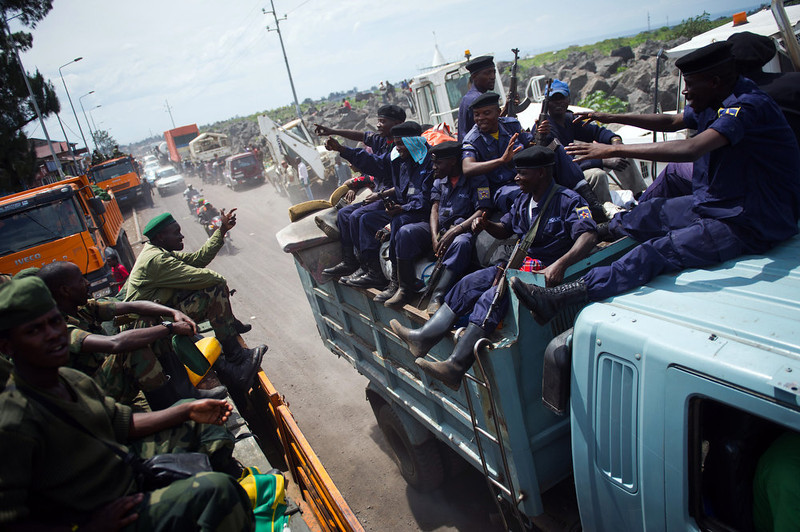 . Congoles M23 rebels (L) pass a truck of police officers as they withdraw on December 1, 2012 from the city of Goma in the east of the Democratic Republic of the Congo. Hundreds of Congolese M23 rebels began a withdrawal on December 1 from Goma as promised under a regionally brokered deal, after a 12-day occupation of the city. Around 300 rebels, army mutineers who seized Goma last week in a lightning advance, were seen by an AFP reporter driving in a convoy of looted trucks north out the main town in Democratic Republic of Congo\'s mineral-rich east. PHIL MOORE/AFP/Getty Images
