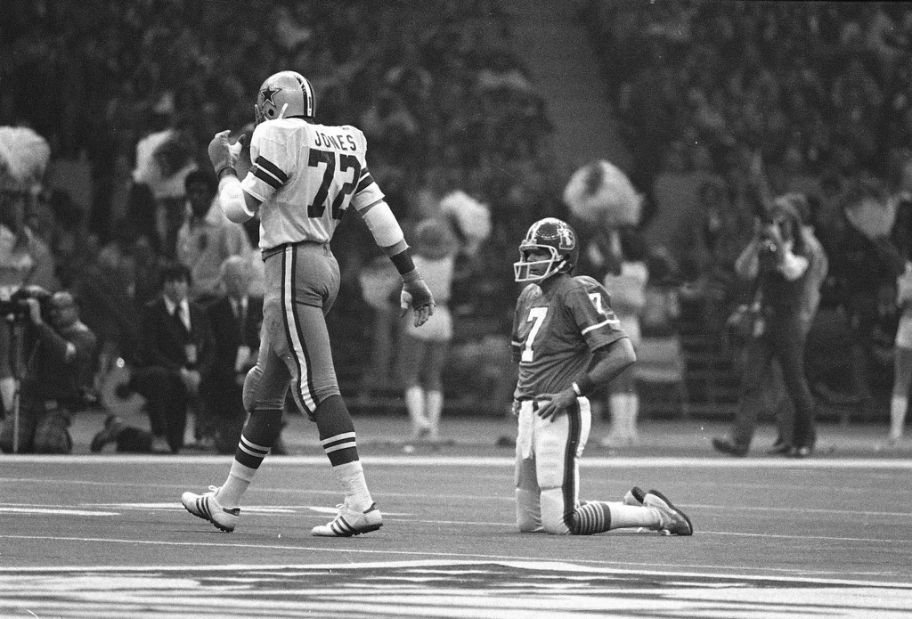 ". Denver Broncos quarterback Craig Morton (7) rests briefly after being sacked by Dallas Cowboys defensive end Ed ""Too Tall\"" Jones (72) following the play during Super Bowl XII  in New Orleans.  The Cowboys defeated the Broncos 27-10.  (AP Photo)"