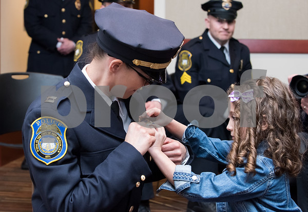 02/15/18 Wesley Bunnell | Staff The New Britain Police Department promoted three of its own including the first female Captain in its history. Newly promoted Captain Jeanette Portalatin has her badge pinned on her uniform with the help of her six year old daughter Mika.