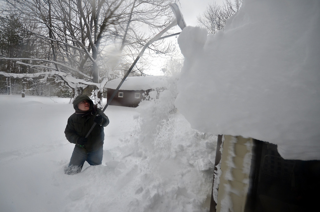 . Mike Ostrander tries to remove some of the five feet of snow from his roof on November 20, 2014 in the Lakeview neighborhood of Buffalo, New York. The record setting Lake effect snowstorm dumped up to six feet of snow in less than 24 hours closing a one hundred mile section of The New York State Thruway as well as other major roads around Buffalo. Seven deaths have already been  attributed to the storm and a second round beginning late Wednesday evening will bring up to three more feet of snow overnight and into Thursday.  (Photo by John Normile/Getty Images)