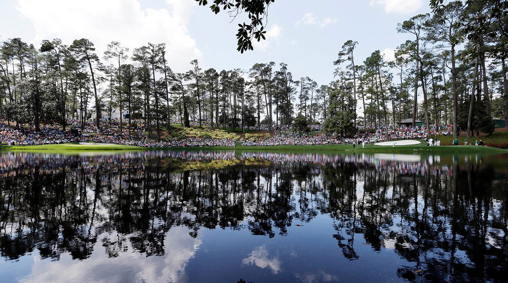 . Spectators sit along the eighth and ninth greens to watch the par three competition at the Masters golf tournament Wednesday, April 9, 2014, in Augusta, Ga. (AP Photo/David J. Phillip)