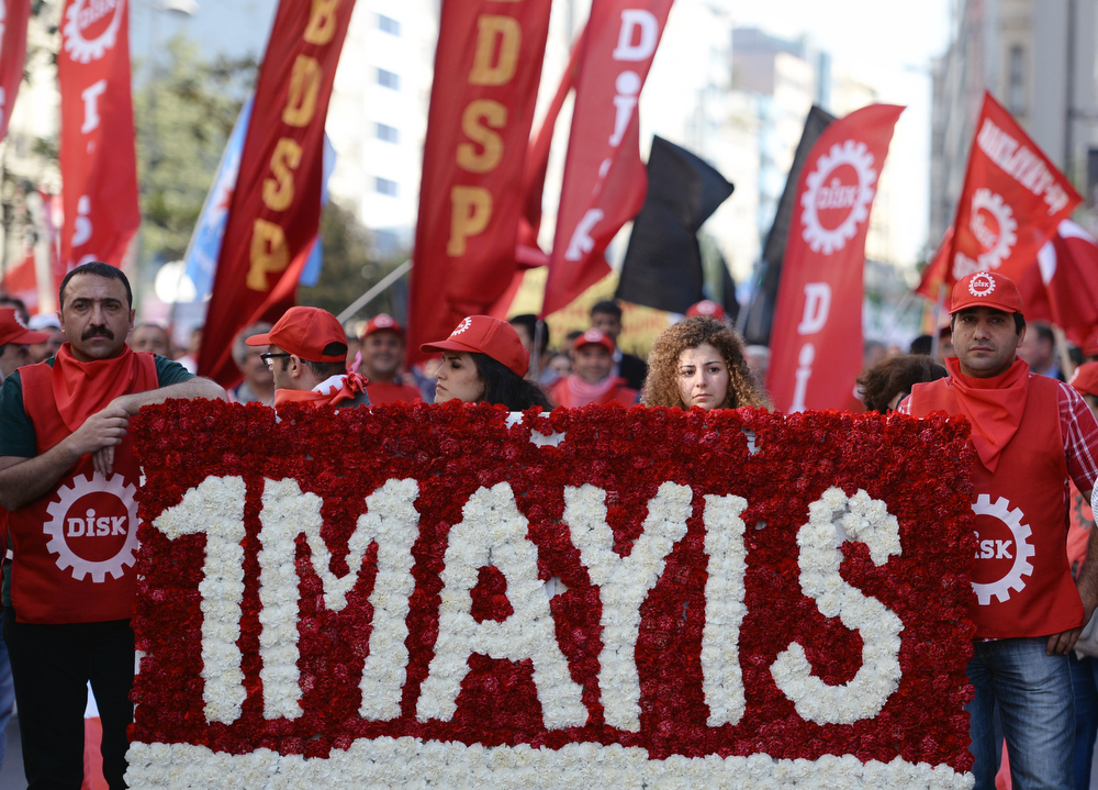 . Workers carry a wreath of carnations before clashes erupted between police and protesters during May Day celebrations in Istanbul, Turkey, Wednesday May 1, 2013. The government, citing security reasons, banned a rally on Istanbul\'s Taksim Square, which is undergoing major renovations. Police fired tear gas to disperse hundreds of demonstrators trying to break through barricades to access the square. (AP Photo)