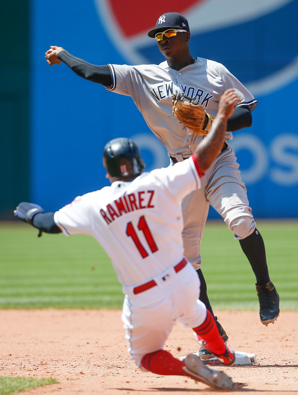 . New York Yankees\' Didi Gregorius, top, forces out Cleveland Indians\' Jose Ramirez (11) at second base and throws out Yonder Alonso at first base to complete the double play during the sixth inning of a baseball game, Sunday, July 15, 2018, in Cleveland. (AP Photo/Ron Schwane)