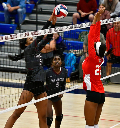 11/1/2018 Mike Orazzi | Staff Farmington High Schools Chardae Saunders (5) and Conard's Trude Davis (22) during the CCC Volleyball Tournament held at Avon High School Thursday night.