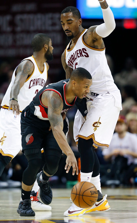 . Portland Trail Blazers\' Damian Lillard (0) tries to drive around Cleveland Cavaliers\' J.R. Smith (5) during the first half of an NBA basketball game, Wednesday, Nov. 23, 2016, in Cleveland. (AP Photo/Ron Schwane)