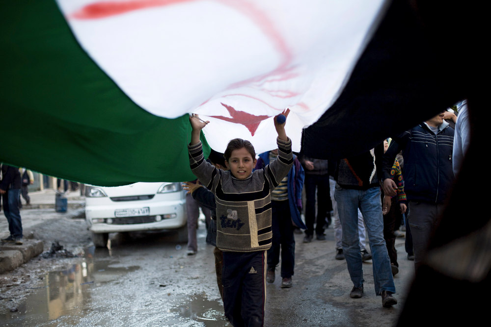. A Syrian child marches under a revolutionary flag during a weekly demonstration in Aleppo, Syria, Friday, Dec. 14, 2012. (AP Photo/Manu Brabo)