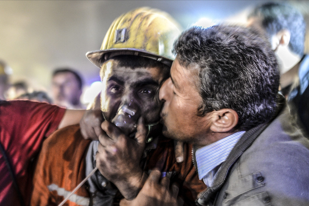 ". A man kisses his son, rescued of the mine, on May 13, 2014 after an explosion in a coal mine in Manisa. At least 157 miners were killed in collapsed coal mine in the western Turkish city of Manisa. ""At least 200-300 workers were working in the mine when an electric fault caused an explosion,\"" the mayor of Soma, a district of Manisa, told private NTV television. AFP PHOTO/BULENT  KILIC/AFP/Getty Images"