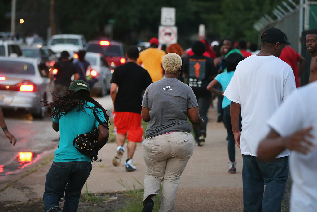. People flee as police advance on protestors firing tear gas and rubber bullets to force them from the business district into nearby neighborhoods on August 11, 2014 in Ferguson, Missouri. Residents and their supporters were protesting the shooting by police of an unarmed black teenager named Michael Brown who was killed Saturday in this suburban St. Louis community. Yesterday 32 arrests were made after protests turned into rioting and looting in Ferguson.  (Photo by Scott Olson/Getty Images)