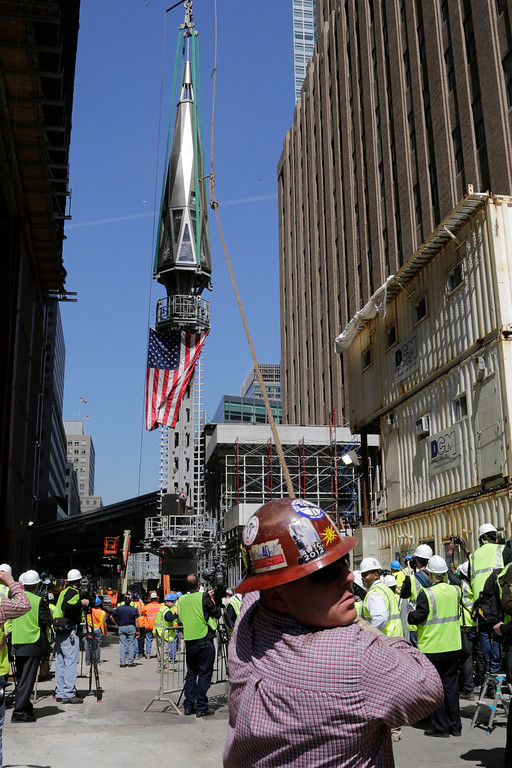 . A worker holds a guide rope as the final piece of spire is hoisted to the roof of One World Trade Center, Thursday, May 2, 2013 in New York.  (AP Photo/Mark Lennihan)