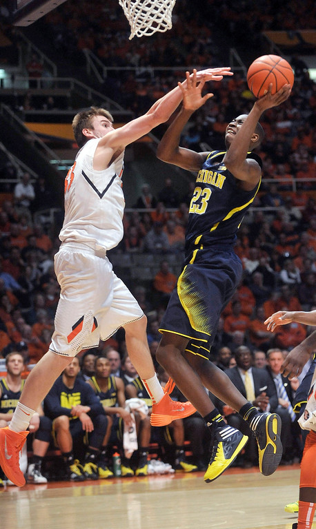 . Michigan guard Caris LeVert (23) goes up with a shot on Illinois forward Jon Ekey (33) during the second half of an NCAA college basketball game Tuesday, March 4, 2014, in Champaign, Ill. (AP Photo/Rick Danzl)