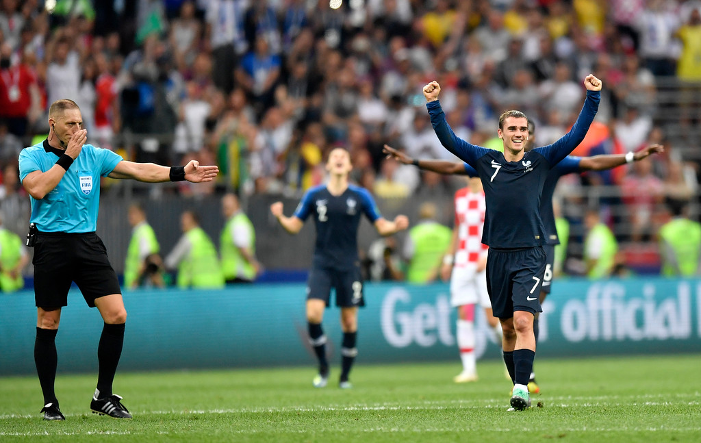 . France\'s Antoine Griezmann, right, celebrates winning the World Cup as referee Nestor Pitana from Argentina, left, blows the final whistle during the final match between France and Croatia at the 2018 soccer World Cup in the Luzhniki Stadium in Moscow, Russia, Sunday, July 15, 2018. (AP Photo/Martin Meissner)