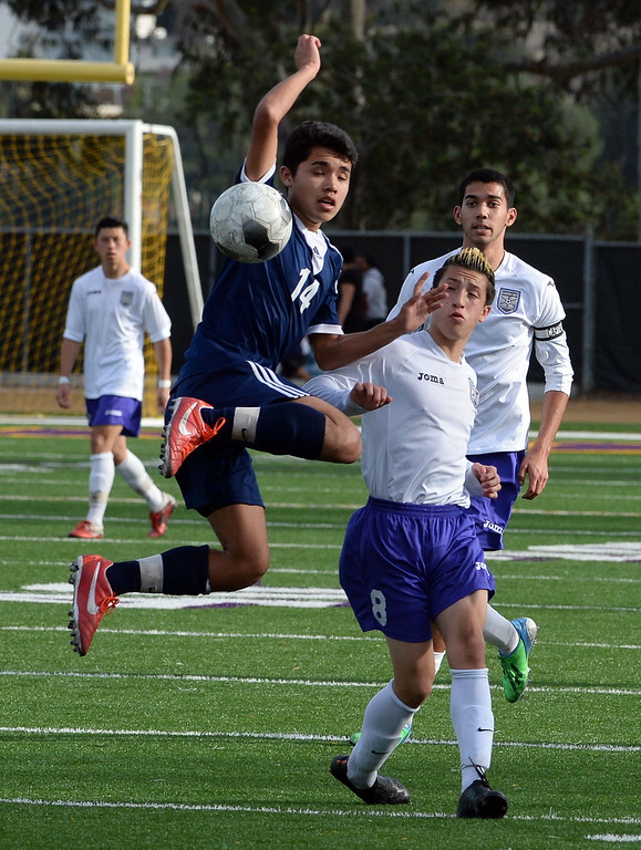 . Baldwin Park\'s Eric Garces (14) goes up high for the ball past Diamond Bar\'s Guy Horcasitas (8) in the first half of a CIF-SS quarterfinal prep playoff soccer match at Diamond Bar High School in Diamond Bar, Calif., on Thursday, Feb.27, 2014. Baldwin Park won 2-1. (Keith Birmingham Pasadena Star-News)