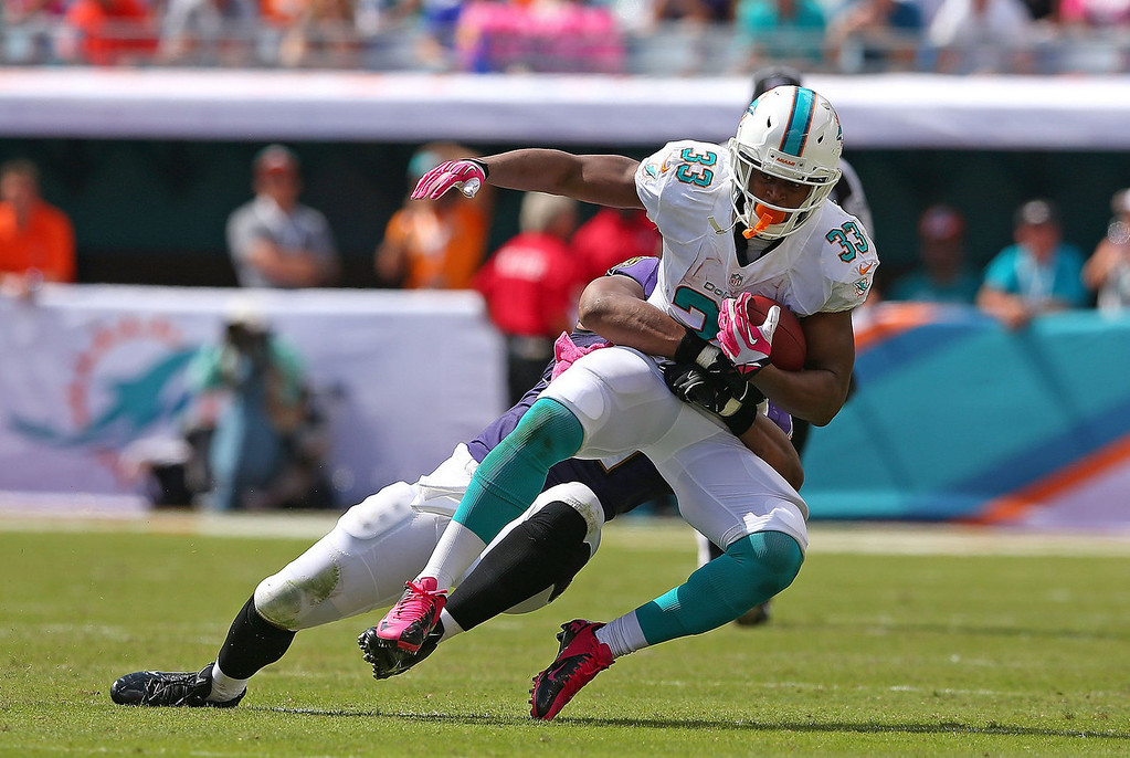. Daniel Thomas #33 of the Miami Dolphins is tackled during a game against the Baltimore Ravens at Sun Life Stadium on October 6, 2013 in Miami Gardens, Florida.  (Photo by Mike Ehrmann/Getty Images)