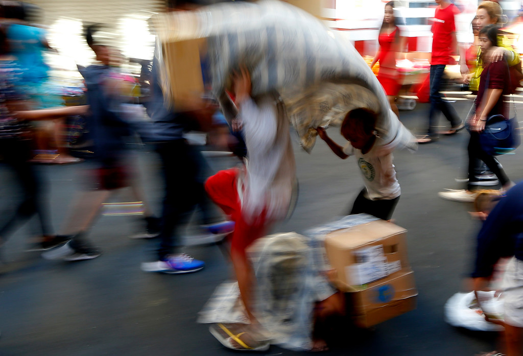. Enterprising Filipino children use improvised lion costumes as they perform lion dance in celebration of the Chinese Lunar New Year Friday, Feb. 16, 2018 at Manila\'s Chinatown district in Manila, Philippines. This year is the Year of the Earth Dog in the Chinese Lunar calendar. (AP Photo/Bullit Marquez)