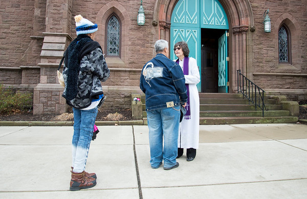 02/26/20 Wesley Bunnell | Staff Pastor Jane Rowe from South Congregational Church stood outside of the church on Ash Wednesday for anyone that wanted to receive ashes. Two passersby stop to receive ashes from Pastor Rowe.