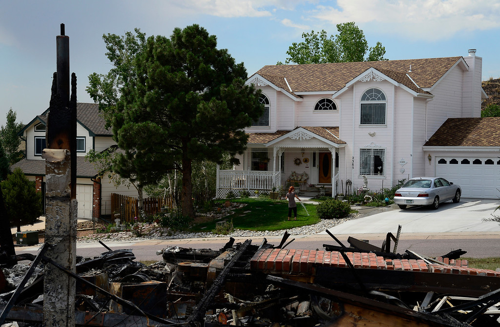 . Sharon Dougherty waters the lawn at her home on Rossmere St. in the Mountain Shadows subdivision in Colorado Springs, July 1, 2012, the first day evacuees were allowed to return to the subdivision. Dougherty\'s home survived the Waldo Canyon fire that burned over 350 homes unscathed.  Mahala Gaylord, The Denver Post