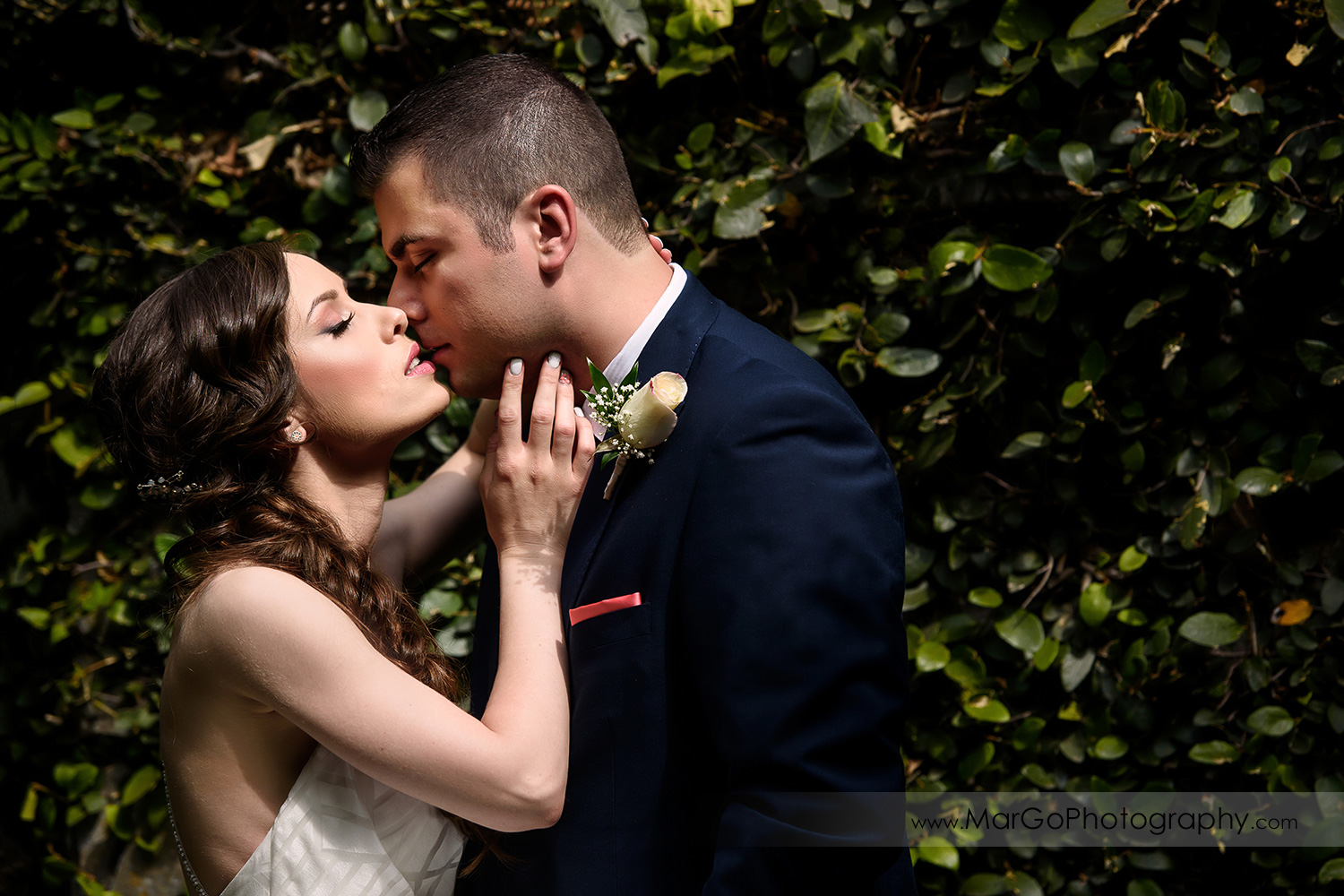bride and groom kissing on the green wall at Saratoga Foothill Club