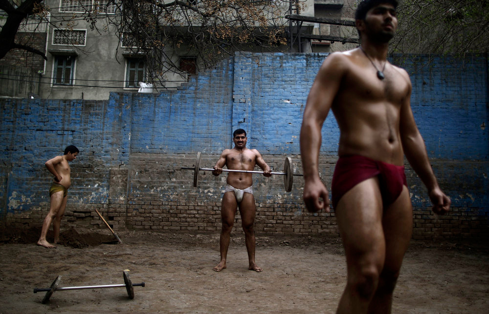 Description of . Pakistani Kushti wrestlers warm up in the ring before fighting as part of their daily training, at a wrestling club in Lahore, Pakistan, Tuesday, Feb. 26, 2013. Kushti, an Indo-Pakistani form of wrestling, is several thousand years old and is a national sport in Pakistan. (AP Photo/Muhammed Muheisen)