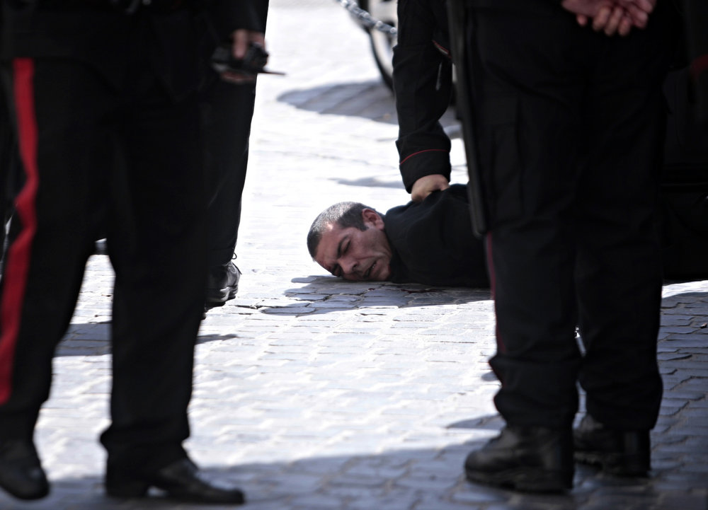 . A man believed to be the assailant lies on the ground detained by police after a shootout outside the Chigi Premier\'s office, in Rome, Sunday, April 28, 2013. Two paramilitary police officers were shot and wounded outside the Italian premier\'s office as the new leader Enrico Letta was sworn in about a kilometer (half-mile) away. It was unclear if there was any connection between the events. (AP Photo/Mauro Scrobogna, Lapresse)