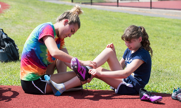 08/08/19 Wesley Bunnell | Staff Volunteer Haley Mistretta, L, assists Katie Brennan with her cleats while preparing for the track and field event at the Hospital for Special Care's Ivan Lendl Adaptive Sports Camp at Berlin High School on Thursday August 9, 2019. Katie is a member of the team which placed second at the Junior Nationals 2019 championship event in Minnesota.