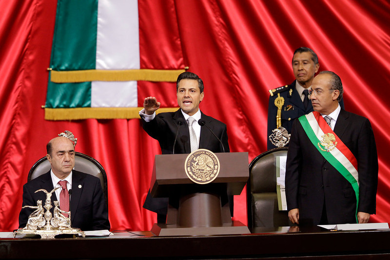 . Enrique Pena Nieto, center, is sworn in as Mexico\'s new president as outgoing President Felipe Calderon, right, still wearing the presidential sash, watches at the National Congress in Mexico City, Saturday, Dec. 1, 2012. Pena Nieto took the oath of office as Mexico\'s new president on Saturday, bringing the old ruling party back to power after a 12-year hiatus amid protests inside and outside the congressional chamber where he swore to protect the constitution and laws of the land.  At left is Jesus Murillo Karam, president of the lower house of Congress. (AP Photo/Alexandre Meneghini)