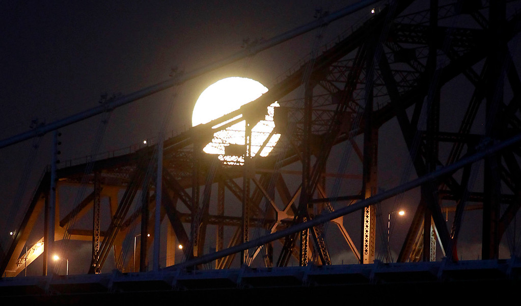 . A full moon rises behind the cantilever section of the Bay Bridge Wednesday evening Aug. 21, 2013. The 78-year-old span is retiring next week as the new $6.4 billion replacement span takes its place. (Karl Mondon/Bay Area News Group)