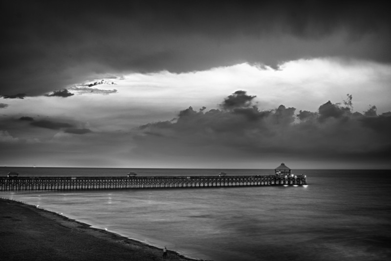This was taken during a storm at Folly Beach Fishing Pier in August. The storm swelled in from the sea and made for very dramatic skies and added some wonderful lightening. Originally I was going to crop or clone out the fella taking the picture on the tripod but thought that it added life and character to shot so I kept it in there.