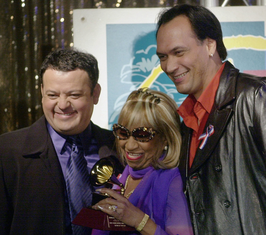 ". Actor Jimmy Smits, right, and comedian Paul Rodriguez, left, pose with Celia Cruz after they presented her with a Latin Grammy Award, Tuesday, Oct. 30, 2001, at a news conference in Los Angeles. Cruz\'s ""Siempre Vivire\"" won for best traditional tropical album.  (AP Photo/Nick Ut)"