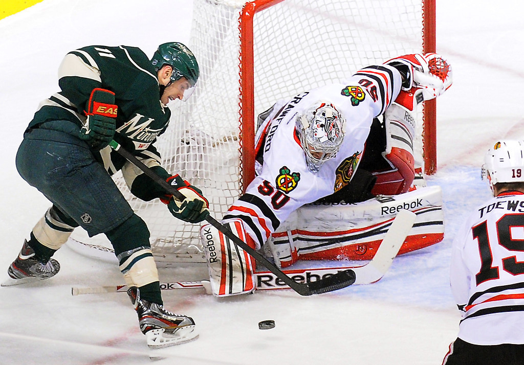 . Minnesota left wing Zach Parise tries to squeeze a shot past Chicago goalie Corey Crawford in the first  period. (Pioneer Press: John Autey)