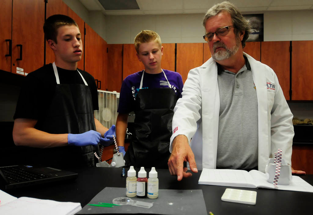 . Teacher Ken Meyer, right, explains how to test various unknown powdery substances to juniors Corey Linton, left, and Garrett Dey. (Pioneer Press: Scott Takushi)