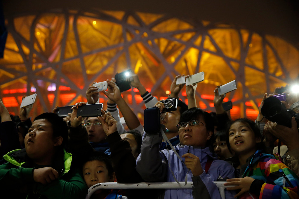 """. People use their smartphones to take photos of the French production company La Machine\'s latest creation \""""the Long Ma\"""" or Dragon Horse and the mechanical spider also known as La Princesse perform in front of the Bird\'s Nest Stadium in Beijing, China Sunday, Oct. 19, 2014. The performance, which attended by French Foreign Minister Laurent Fabius and his Chinese counterpart Wang Yi, marked the climax of celebrations for the 50th anniversary of Sino-French diplomatic relations. (AP Photo/Andy Wong)"""