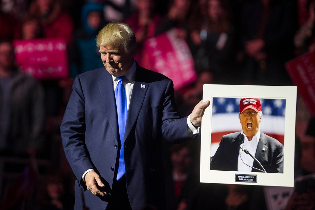 . MANCHESTER, NH - NOVEMBER 07:  Republican presidential candidate Donald Trump holds up a picture of himself that supporter handed him at the end of his rally at the SNHU Arena on November 7, 2016 in Manchester, New Hampshire. With one day until the election, both candidates and their surrogates are holding campaign rallies in battleground states across the nation.  (Photo by Scott Eisen/Getty Images)