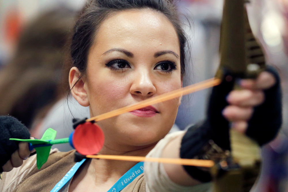 . Krystle Anderson demonstrates the Legends Longbow from Zing at the American International Toy Fair, Monday, Feb. 11, 2013 in New York. More than 1,000 international toy manufacturers and distributors market their products to the toy industry at the annual fair. (AP Photo/Mark Lennihan)