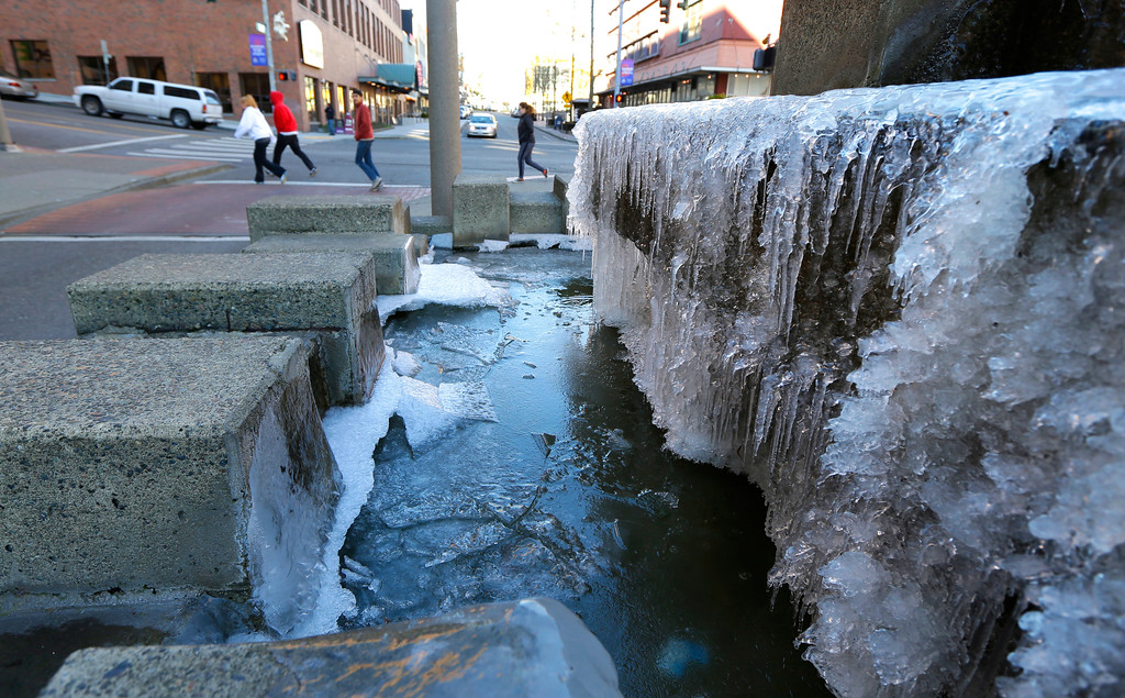 . Pedestrians walk past a frozen fountain Wednesday, Jan. 4, 2017, in Tacoma, Wash. Wet winter weather slammed much of the West on Wednesday, with storms dropping several inches of snow on one Oregon city and several feet of the white stuff predicted high in the Sierra Nevada. (AP Photo/Ted S. Warren)