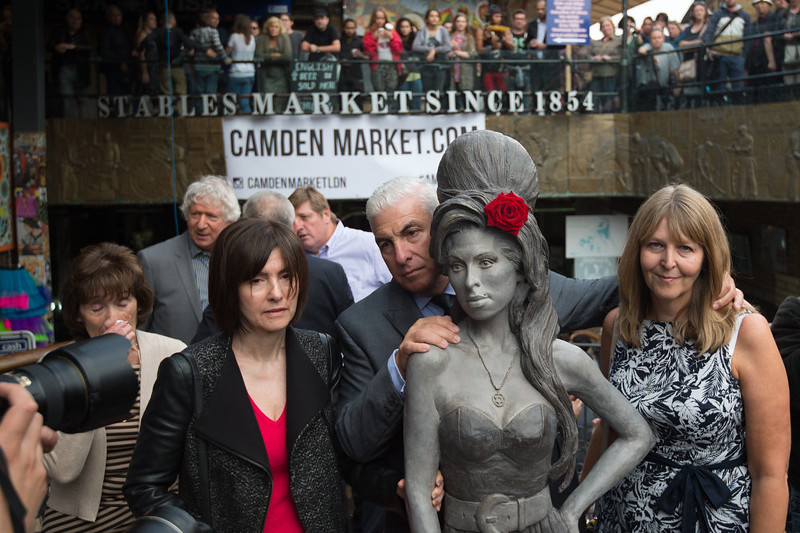 . Mitch Winehouse, centre, poses for a picture with a statue of his late daughter, Amy Winehouse, accompanied by friends and family after it was unveiled in Camden\'s Stables Market, in London, England, Sunday, Sept. 14, 2014. Three years after her death the unveiling coincides with what would have been her 31st birthday. (AP Photo/Tim Ireland)