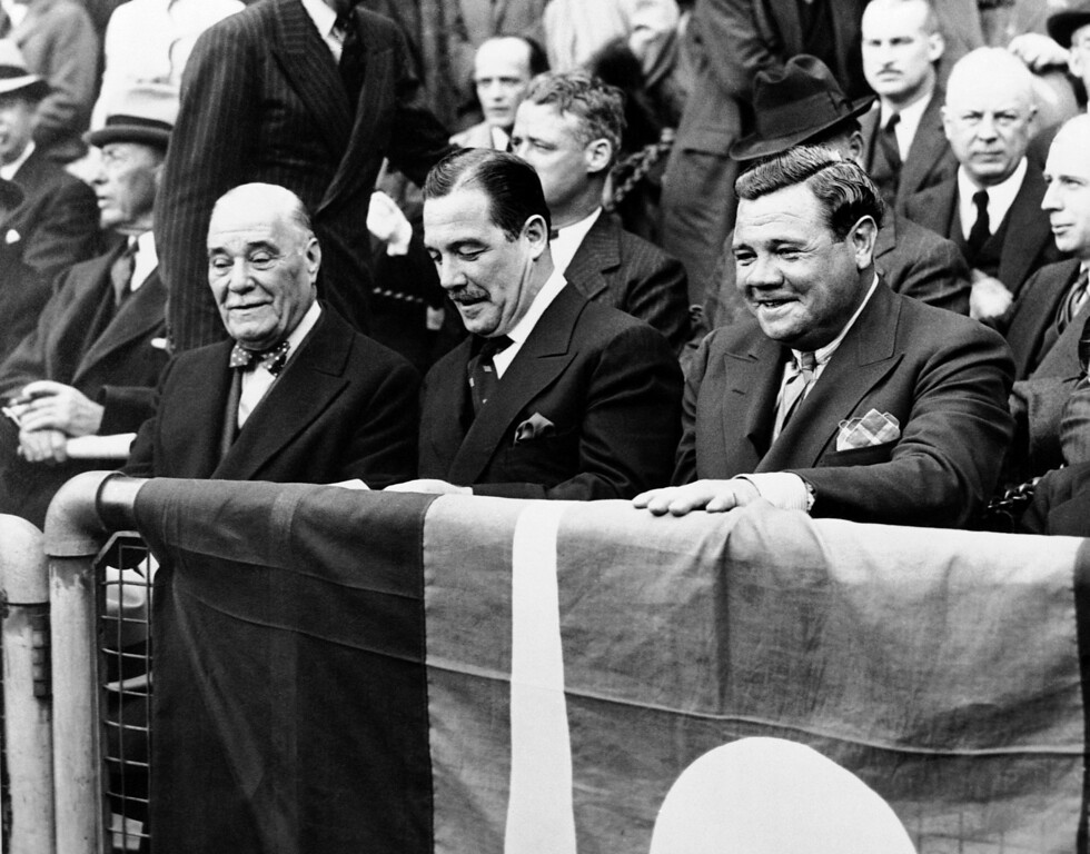 . Babe Ruth, right, embittered by his lack of success at landing a managerial berth, last winter announced he�d never attend another ball game. But in company of Col. Jake Ruppert, left, his old New York Yankee Boss, and Grover �Halen, New York World fair manager, he was in the front row as the New York baseball season opened in New York, April 19. The Bambino, who once collected $80,000 per from Ruppert, saw the Giants beat the Boston Bees. Year not provided. (AP Photo)